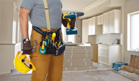 Builder handyman with construction tools on house background.