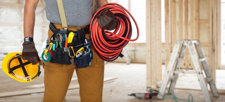 Builder handyman with construction tools in new house background. Stockfoto