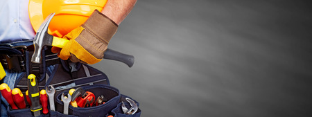 Builder handyman with construction tools on gray background.