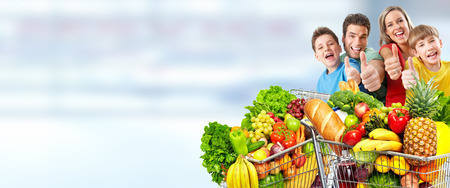 Happy family  with grocery shopping cart over blue abstract background.