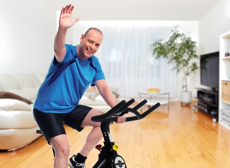 Man exercising on bicycle trainer. Dieting and sport background.
