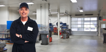 Mature smiling auto mechanic over garage background.