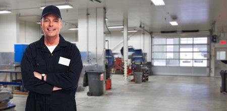 Volwassen lachende automonteur boven garage achtergrond. Stockfoto - 54200176