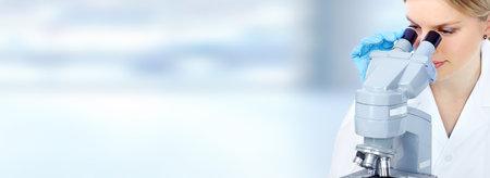 Medico donna che lavora con un microscopio scientifico microscopio. Medical concetto di assistenza sanitaria ricerca di sfondo. Archivio Fotografico - 54200283