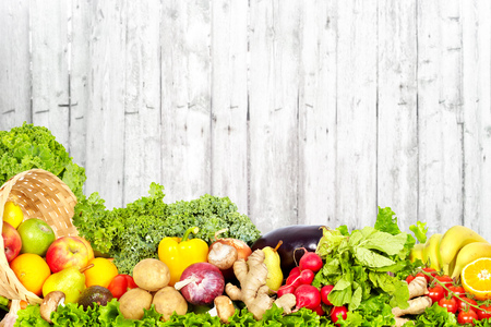 Vegetables and fruits on vintage wooden wall background.