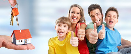 Happy family with children and small house. Construction and real estate concept. Stock Photo
