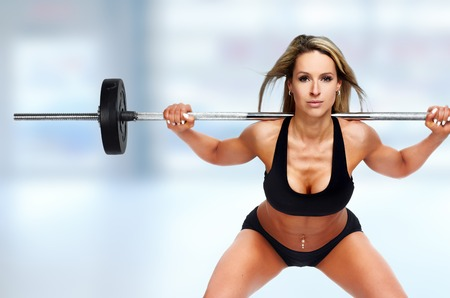 Young beautiful woman doing squat with barbell over blue background. Banque d'images