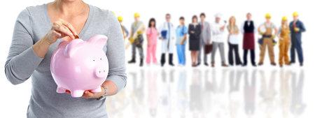 Manos de mujer con una hucha rosa. concepto de ahorro de dinero.