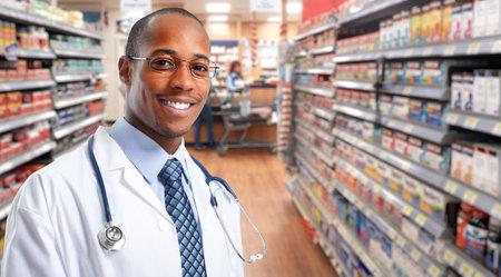 farmacéutico africano-americano sobre el fondo de la farmacia. Foto de archivo