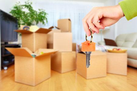 Mano con llave de la casa. Inmobiliario y fondo en movimiento. Foto de archivo