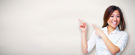 Young asian business woman presenting copyspace gray background. Banque d'images