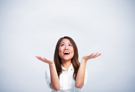Happy asian business woman over blue background.