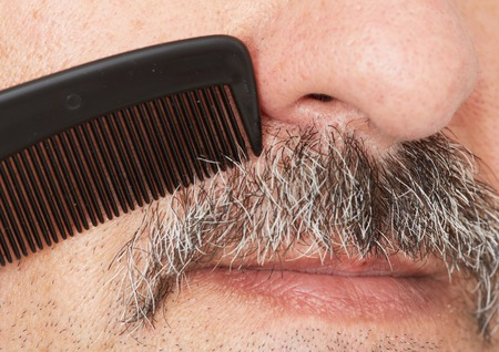 Man combing his mustache with black comb.