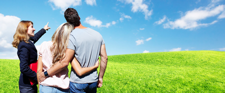 Real Estate agent woman with couple clients over landscape background. 版權商用圖片