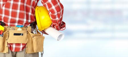 Travailleur de la construction avec une ceinture d'outils sur fond bleu. Banque d'images - 55936687