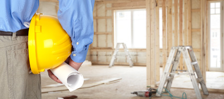 Assistente tecnico con il casco e blueprint su sfondo interno della casa.