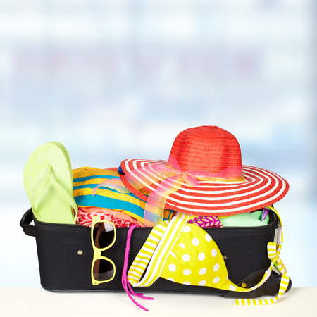 Suitcase ready for vacation with bikini and sunglasses. Stock Photo