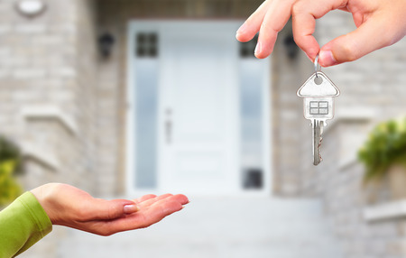 집 열쇠와 손입니다. 건설 및 부동산 개념이다.
