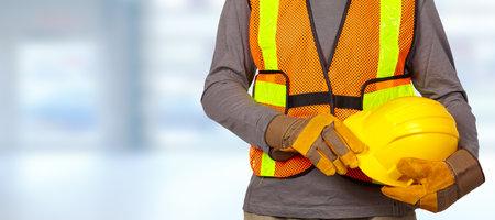 オレンジ セキュリティ ベストのヘルメットと建設労働者。 写真素材 - 56592817