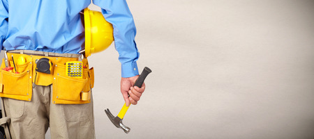 Construction worker with a tool belt over gray background.