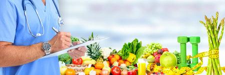 Handen van medische arts over groenten en fruit achtergrond.