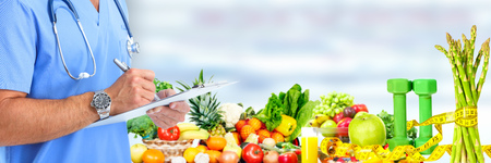 Hands of medical doctor over fruits and vegetables background.