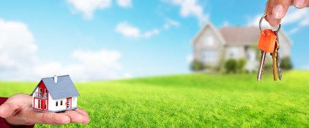 Hand mit einem kleinen Haus und Schlüssel. Bau und Immobilien-Konzept.