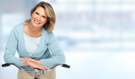 Linda mulher sênior com bicicleta sobre fundo desfocado.