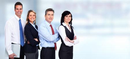 Grupo de jóvenes hombres de negocios sonriente sobre fondo azul.