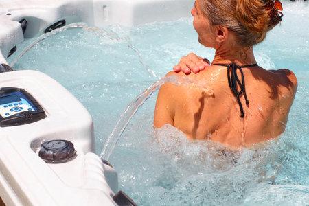 Mujer hermosa joven que se relaja en una bañera de hidromasaje.