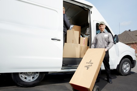 Group of delivery men with packages. Transportation and shipping. Stock Photo