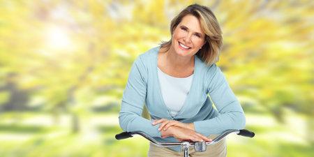 흐린 된 배경 위에 자전거와 함께 아름 다운 수석 여자. 스톡 콘텐츠