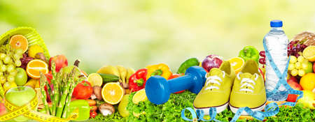 Fresh fruits and vegetables over green background. Standard-Bild