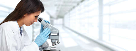 Chinese scientist woman working with microscope in laboratory. 版權商用圖片