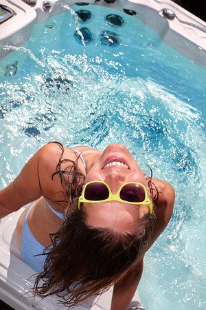 Young beautiful woman relaxing in a hot tub.