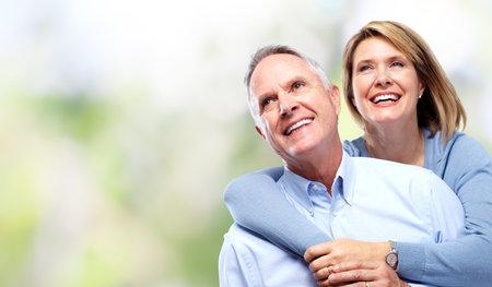 Elderly couple in love over green background.