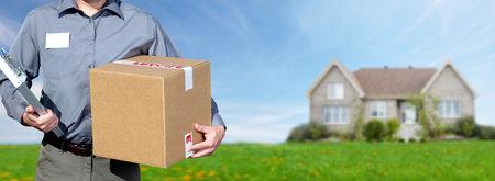 Handen van professionele postbode met een doos over het huis achtergrond. Stockfoto - 61494435
