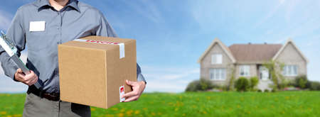 Hands of professional postman with a box over house background.