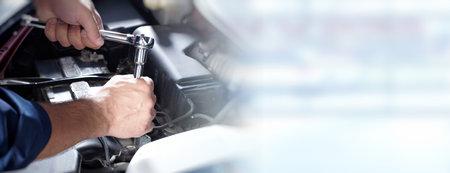 Handen van automonteur met moersleutel in auto reparatie service. Stockfoto