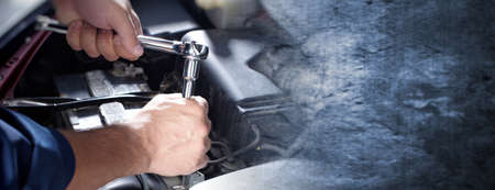 Hands of car mechanic with wrench over dark wall background.