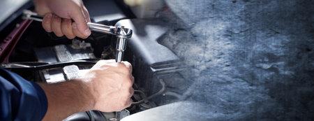 Ręce mechanik samochodowy z kluczem na ciemnym tle ściany. Zdjęcie Seryjne