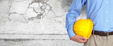 Construction worker with helmet over gray wall background.