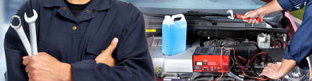 Handen van automonteur met sleutel en auto-accu-oplader.