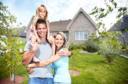 Glückliche Familie mit Kindern in der Nähe von neuen Haus. Bau und Immobilien-Konzept. Standard-Bild