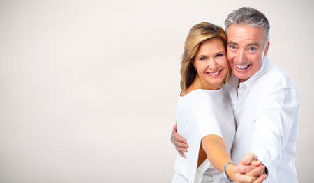 Elderly couple in love over gray background.