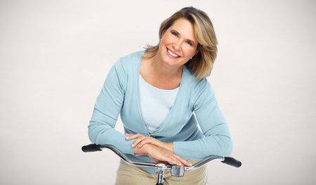 Mooie senior vrouw met fiets over onscherpe achtergrond.