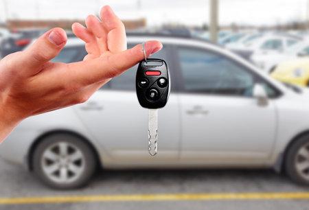 Autohandelaar hand met de sleutel. Auto dealer en verhuur concept achtergrond.
