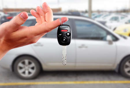 Car dealer hand with key. Auto dealership and rental concept background.