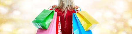 Customer woman with shopping bags over golden background