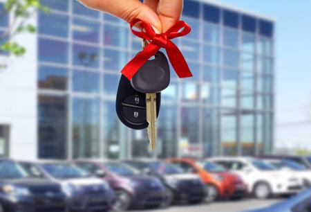 자동차 딜러 손으로 키입니다. 자동차 대리점 및 임대 개념 배경입니다.